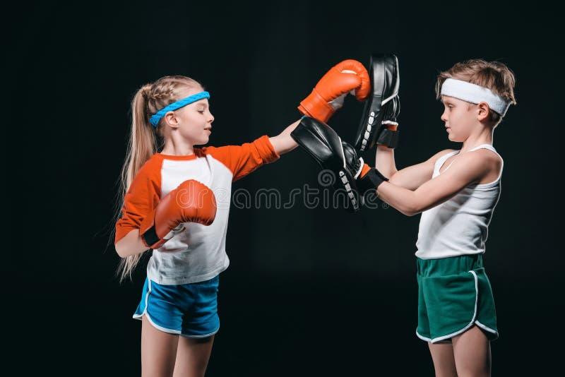 假装拳击的孩子侧视图隔绝在黑色 库存照片