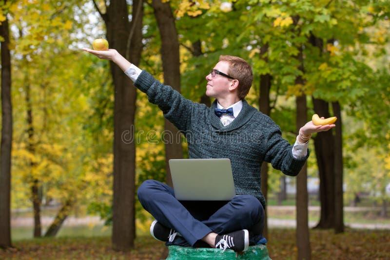 假装是在哲学家姿势的一个雕象在选择一个苹果或一个香蕉前在的垫座的一个人 免版税库存图片