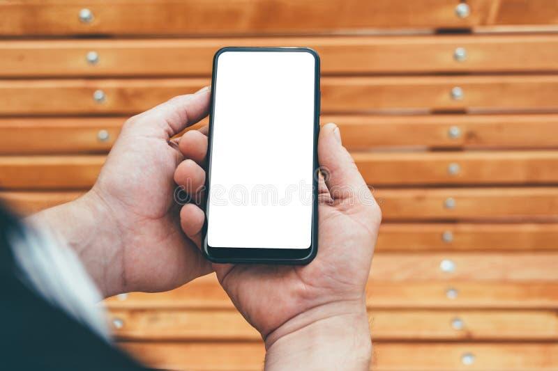 假装智能手机在一个人的手上,以一个长木凳为背景 图库摄影
