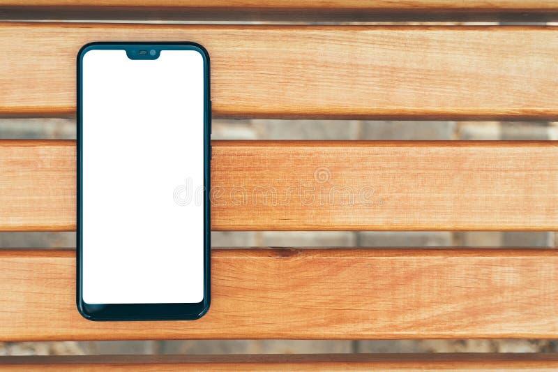 假装智能手机特写镜头,以一个长木凳为背景 免版税库存照片