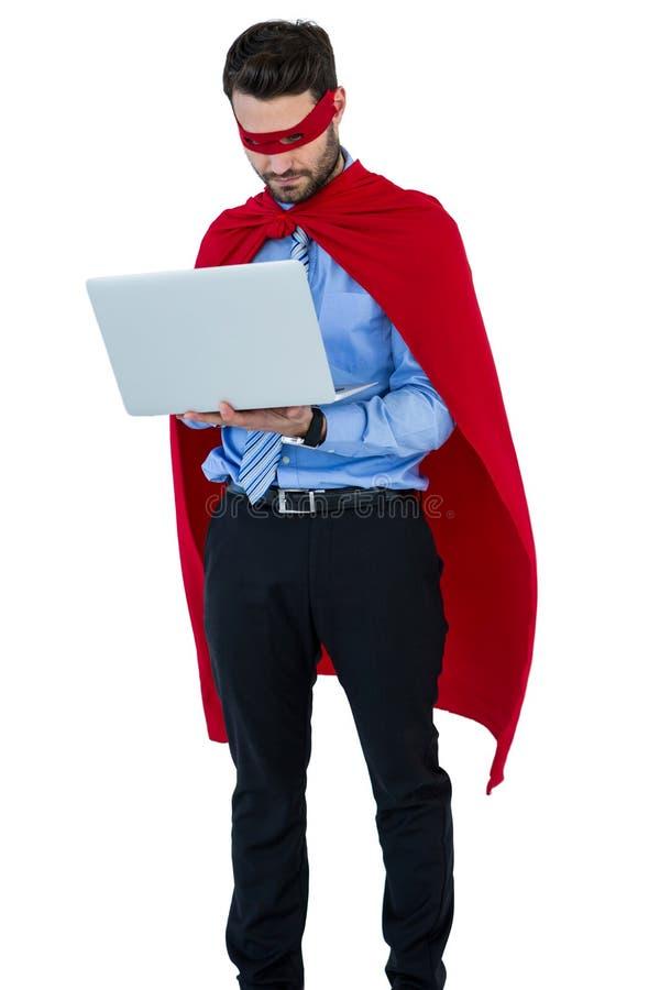 假装的商人是使用膝上型计算机的一位特级英雄 库存图片