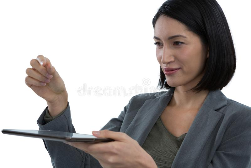 假装的女实业家拿着无形的对象,当使用数字式片剂时 库存图片