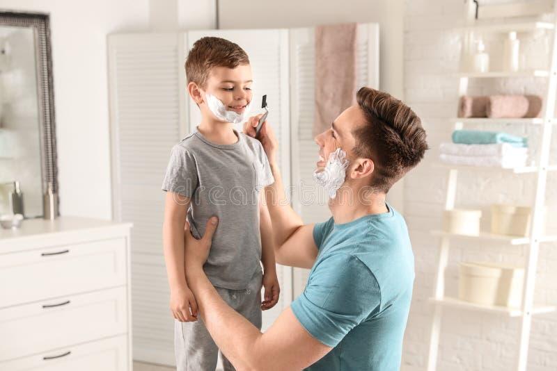 假装的爸爸刮他的小儿子 库存图片