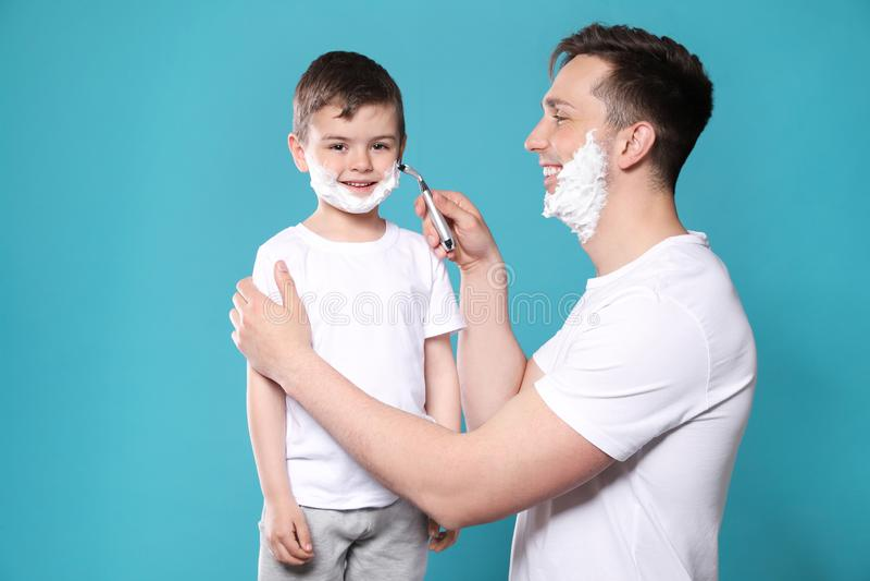 假装的爸爸刮他的小儿子 免版税库存照片