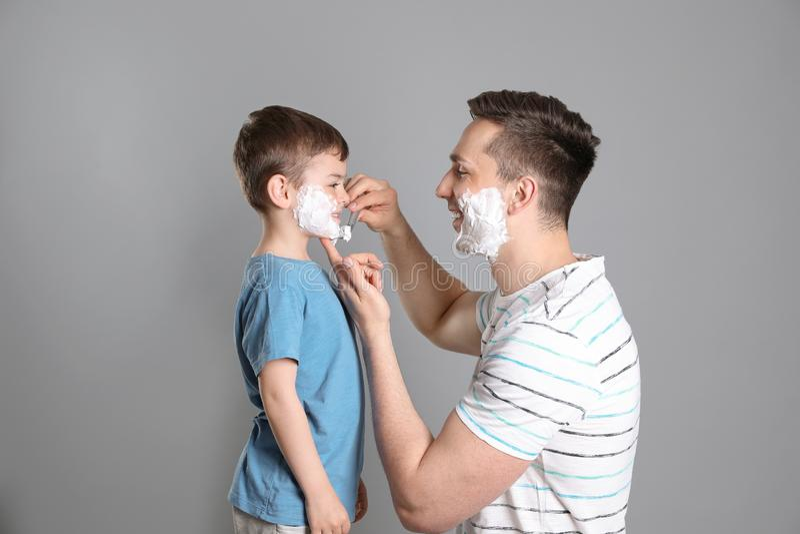 假装的爸爸刮他的小儿子 免版税图库摄影
