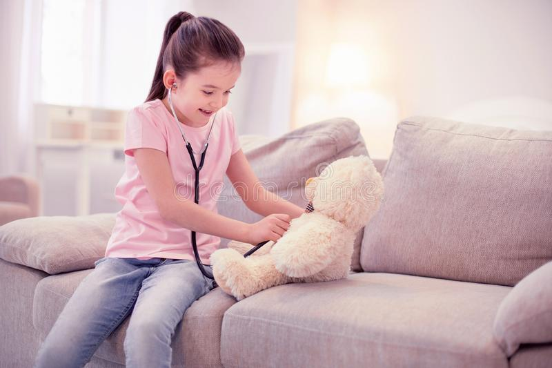 假装逗人喜爱的女孩是使用与她的玩具熊的医生 免版税图库摄影