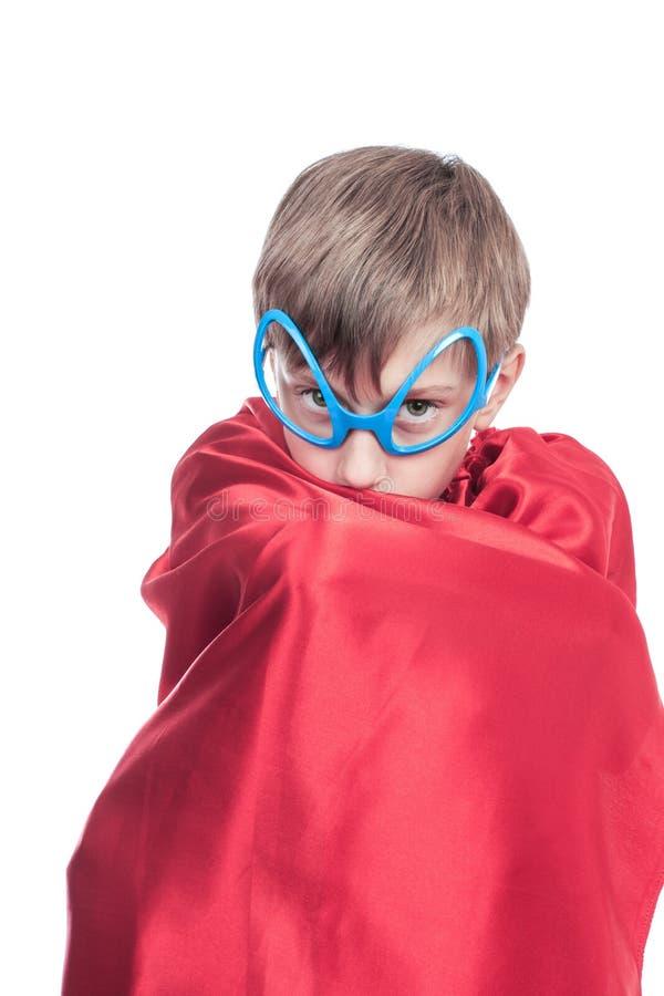 假装滑稽的逗人喜爱的小孩是掩藏在他的海角的超级英雄 库存照片