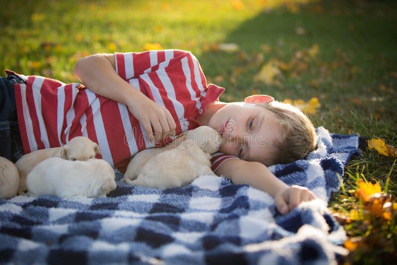 偎依与逗人喜爱的棕褐色的小狗的小男孩 库存照片