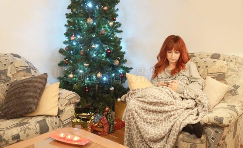 偏僻和哀伤的女孩看看她的手机在圣诞夜 免版税库存照片