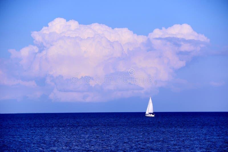 偏僻的白色游艇在蓝色海 免版税库存图片