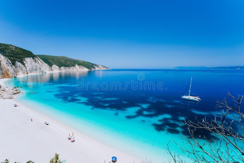 偏僻的白色筏游艇漂泊在清楚的蓝色加勒比喜欢海水 游人在海滩的娱乐活动与 库存照片