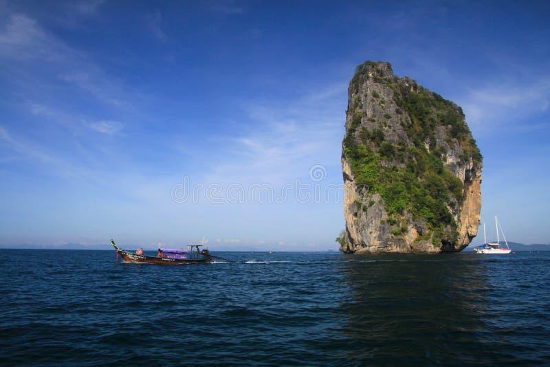偏僻的石灰石岩石在Ao Nang,甲米府,泰国附近的深蓝色安达曼海 免版税图库摄影