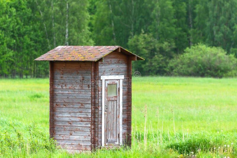 偏僻的谷仓在绿色领域和森林 免版税库存照片