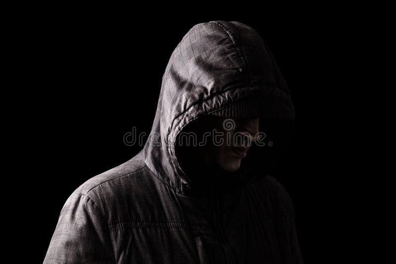 偏僻,沮丧和易碎的白种人或白人掩藏的面孔,站立在黑暗中 库存图片