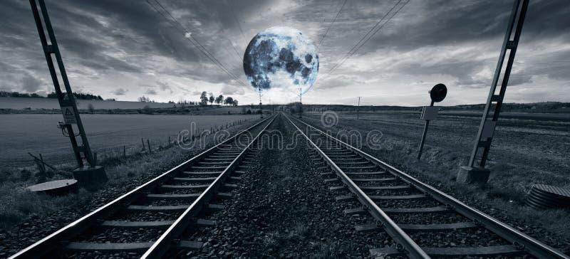 偏僻的火车轨道和超现实的满月 图库摄影
