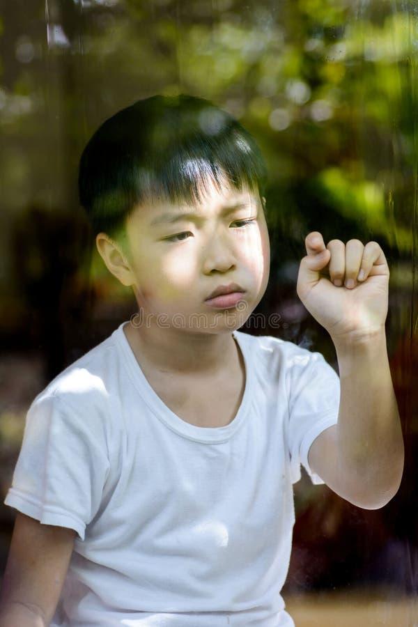 偏僻的男孩和接触窗口 免版税图库摄影