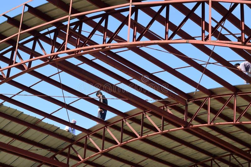 做一个报道的健身房法院的屋顶工作的建筑工人 免版税库存图片