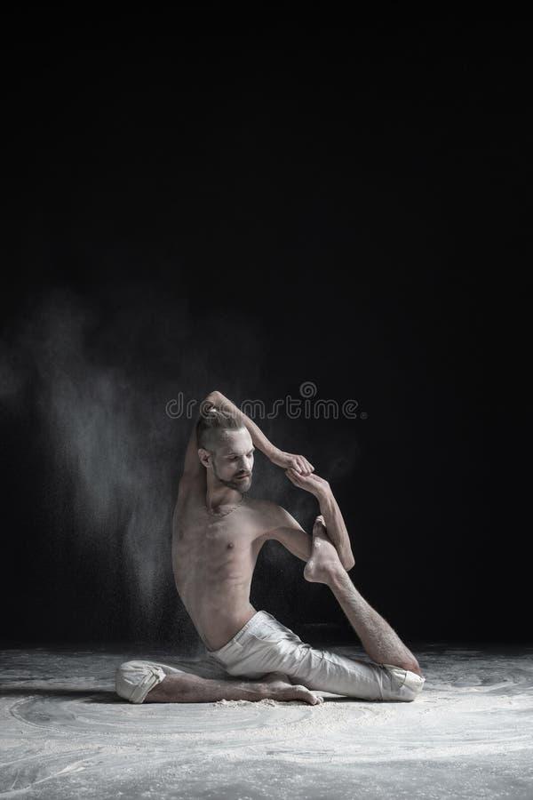 做一个有腿的皇家鸽子姿势, Eka Pada Rajakapotasana的变异的运动的肌肉年轻信奉瑜伽者人 免版税库存图片