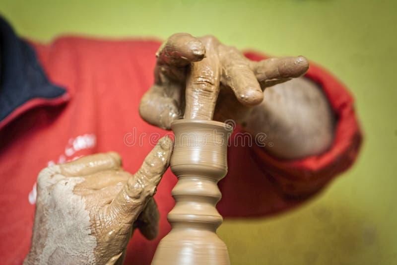 做一个谦逊的蜡烛台的陶瓷工陶瓷用他们的手 免版税库存照片