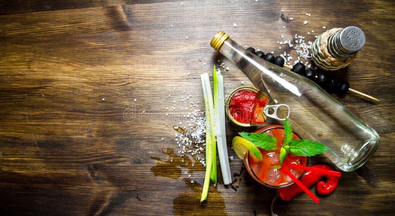 做一个鸡尾酒用伏特加酒、西红柿酱和其他成份在木背景 文本的空位 免版税图库摄影