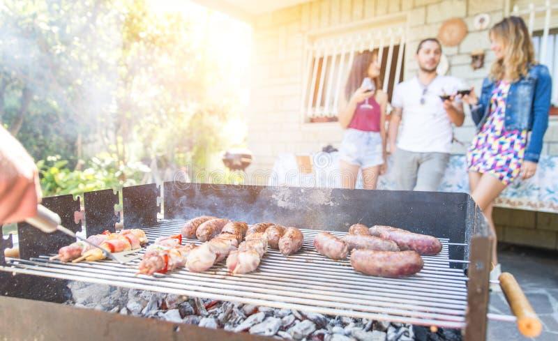 做一串烤肉的小组朋友在后院庭院里 免版税图库摄影