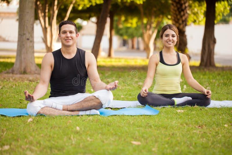 做一些瑜伽的拉丁夫妇 库存图片