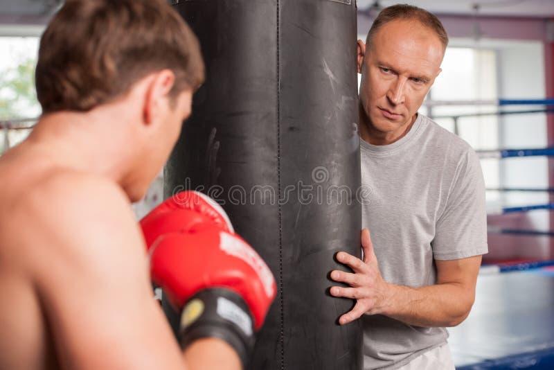 做一些的拳击手和他的教练猛击与袋子 免版税库存照片