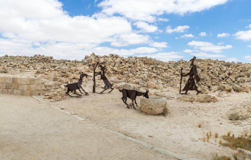 做一位牧羊人的金属剪影有山羊的在Nabataean市Avdat的废墟,在Judean沙漠在以色列 免版税库存图片