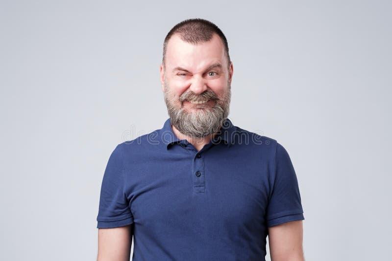 做一副滑稽的微笑的鬼脸的成熟男性 E 库存图片