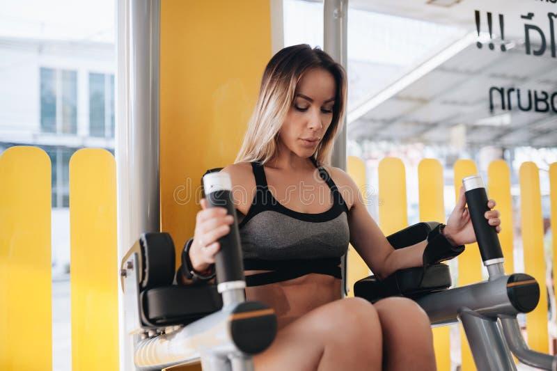 做一名运动的妇女行使abdominals解决在健身房的双杠 库存照片