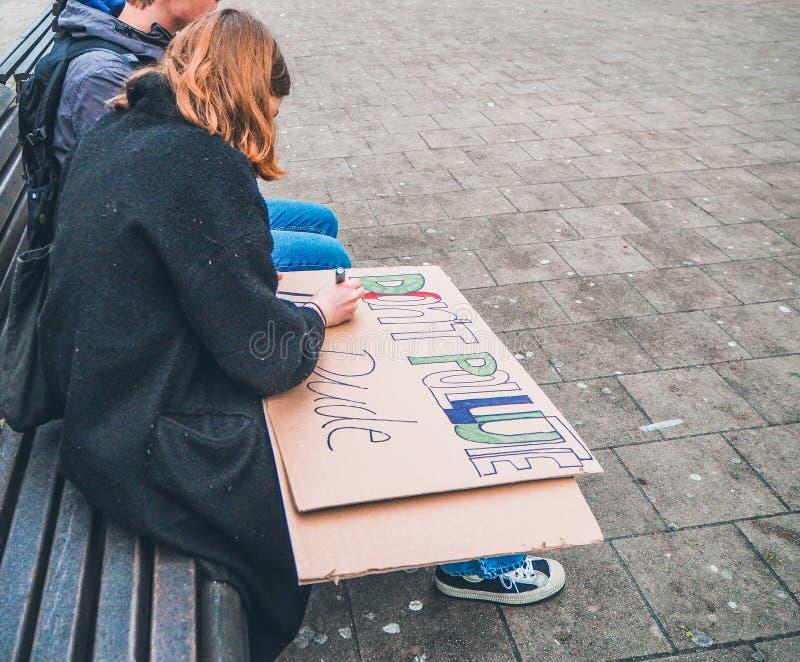做一张手工制造海报的年轻女人作为一个号召在抗议游行期间反对气候变化 免版税库存图片