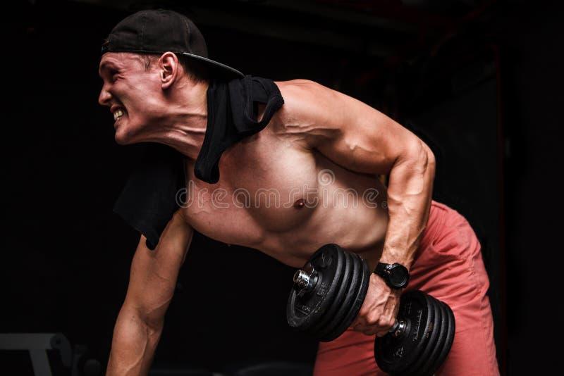 做一胳膊在长凳的年轻英俊的成年男性哑铃行在健身房 免版税库存照片