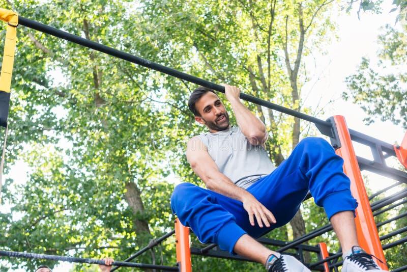 做一胳膊引体向上的强有力的年轻人,当垂悬在一个酒吧在公园时 图库摄影
