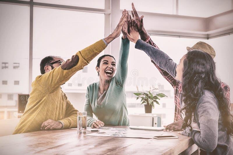 做上流五的快乐的企业队在创造性的办公室 免版税库存照片