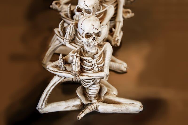 做与一只脚的骨骼瑜伽在他们的坐在橙色的褐色的胳膊下连续弄脏了背景 免版税库存图片