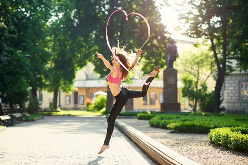 做与一条丝带的舞女竖趾旋转在城市公园 图库摄影