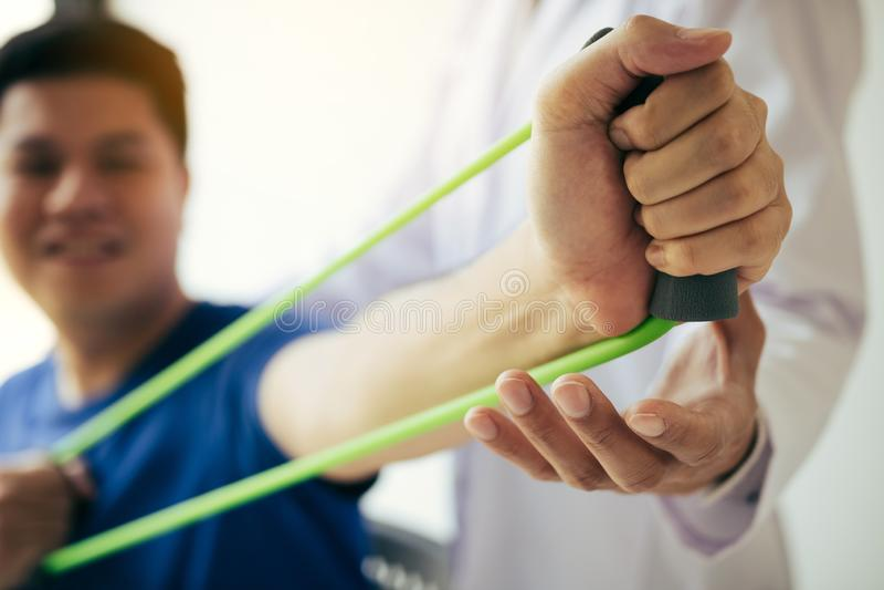 做与一条灵活的锻炼带和一只理疗师手的接近的手患者伸展运动在诊所屋子里帮助 库存图片