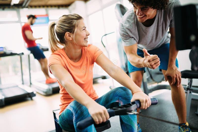 做与个人教练员的年轻美丽的妇女锻炼 库存图片