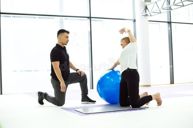 做与个人教练员的成熟妇女锻炼 库存图片