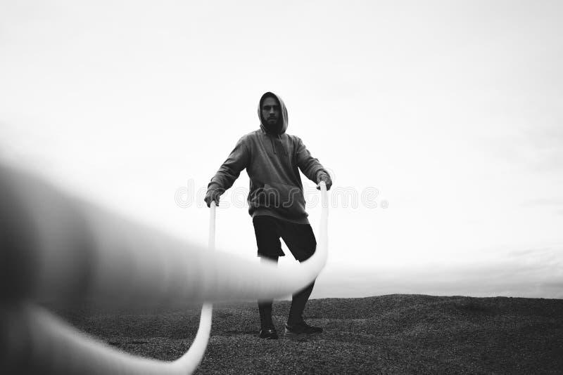 做与争斗绳索的坚强男人强烈的锻炼在海滩 黑白颜色 库存照片