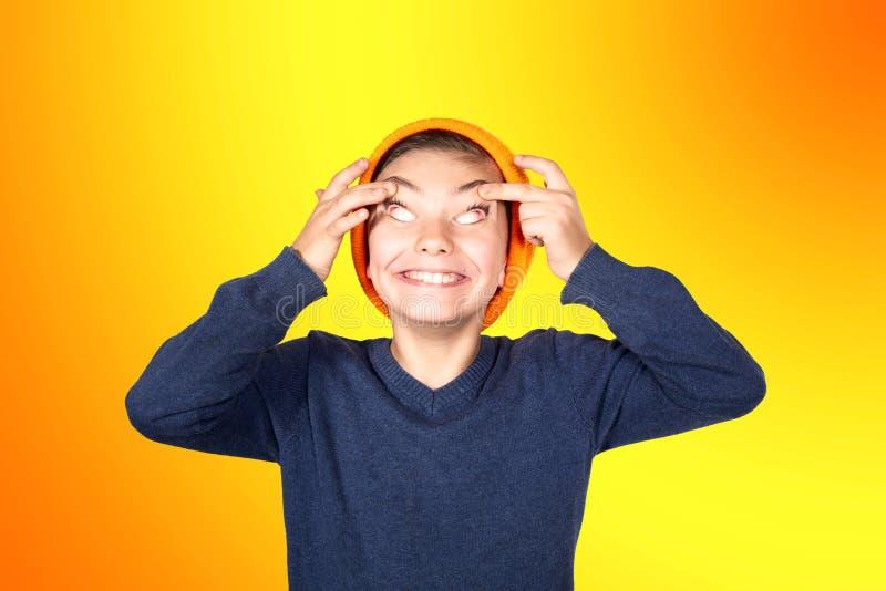 做与他的眼睛的年轻男孩滑稽的面孔 免版税库存照片