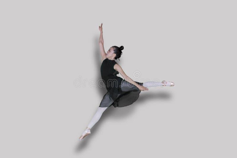 做与优美的姿势的跳芭蕾舞者跃迁锻炼在演播室 免版税库存图片