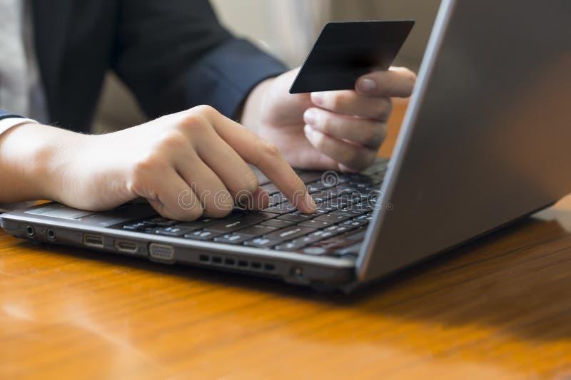 做与信用卡的妇女网上购物在膝上型计算机 图库摄影