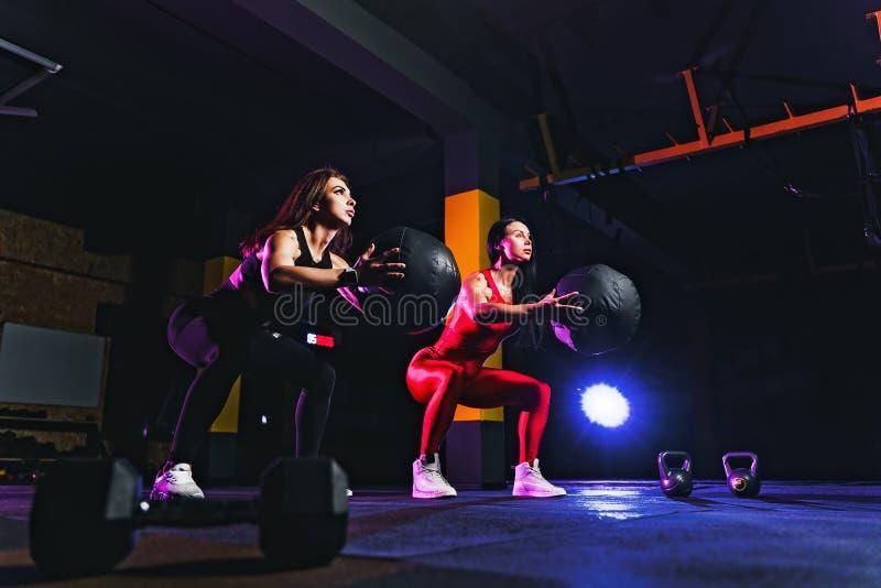 做与健身球的两名体育妇女矮小锻炼 女性行使和舒展与药丸在健身房 免版税图库摄影