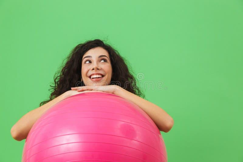 做与健身球的愉快的妇女20s佩带的夏天衣裳照片锻炼在有氧运动期间 免版税库存图片