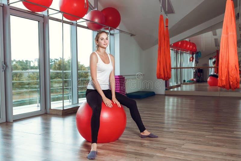 做与健身球的年轻运动妇女锻炼在健身房 免版税库存照片