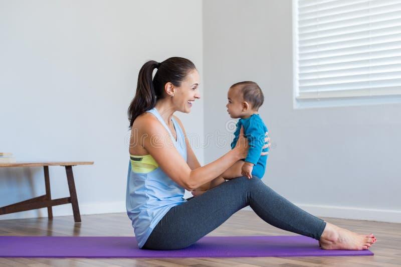 做与儿子的妇女瑜伽 图库摄影