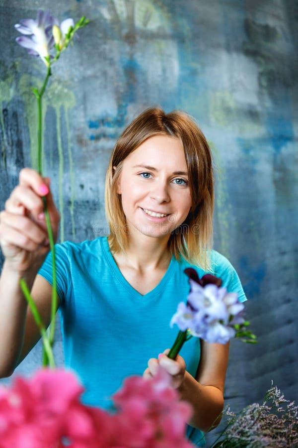做与八仙花属紫色、福禄考和水芋属的迷人的快乐的女性售货员五颜六色的桃红色花束 图库摄影
