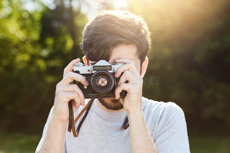 做与减速火箭的照相机的年轻创造性的摄影师照片,拍摄自然美好的风景,当休息在绿色f时 图库摄影
