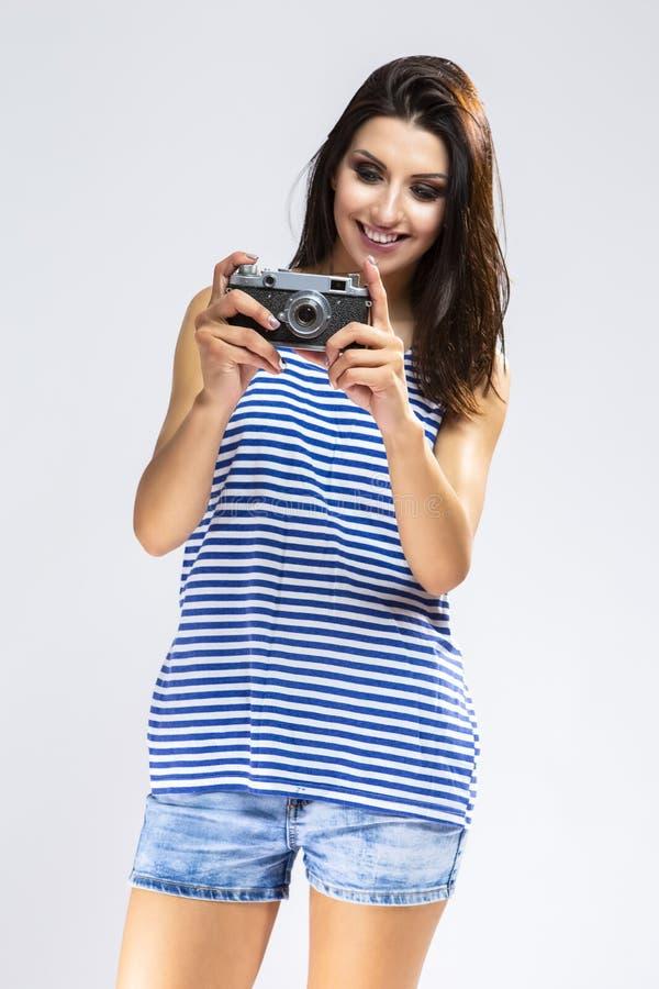 做与古板的影片照相机的运动衫的性感的女孩照片 免版税库存图片